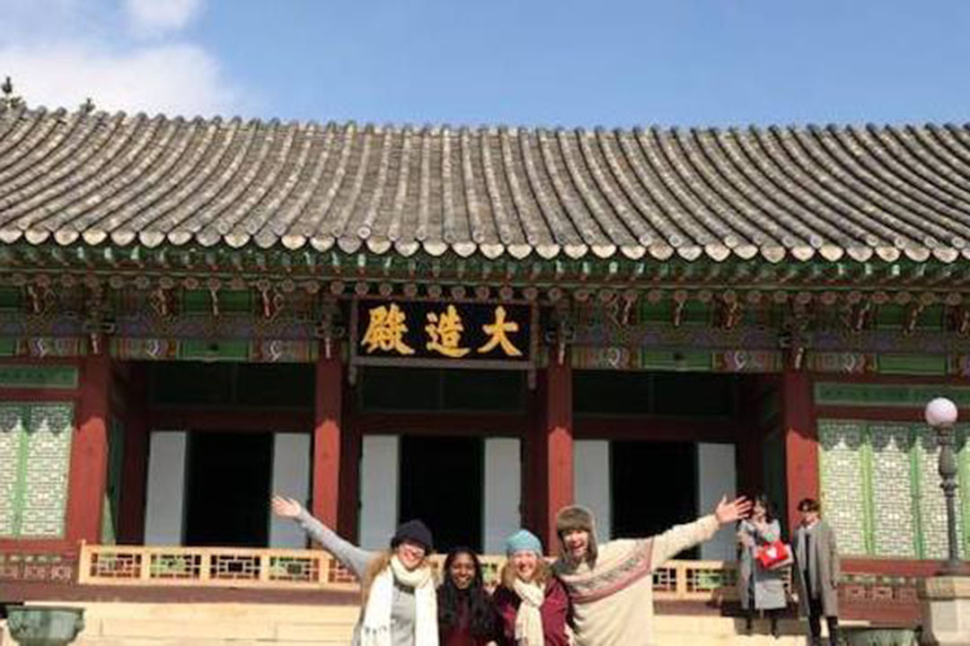 Four students standing in front of a building on Korea University's campus