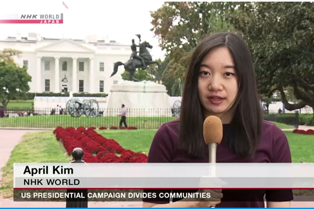 April Kim, BA '17, standing with a microphone outside the White House. NHK World Japan, US Presidential Campaign Divides Communities
